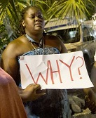 "woman holding sign saying ""Why?"""